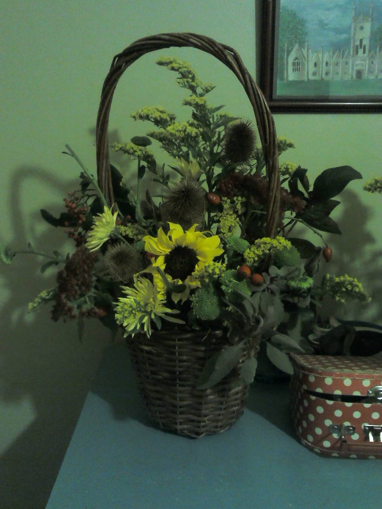 Flower arrangement with sunflower in wicker basket, York